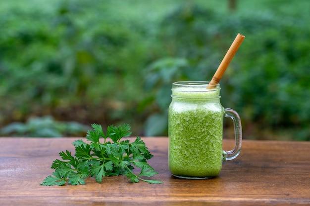 Smoothie vert de persil, avocat, miel et banane dans une tasse en verre sur une table en bois dans un café de jardin, gros plan. concept d'alimentation saine