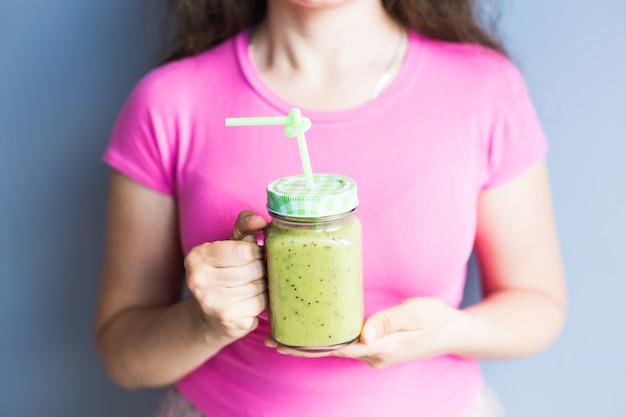 Smoothie vert sain aux asperges dans la main de la femme. vegan, raw food, détox et mode de vie diététique.