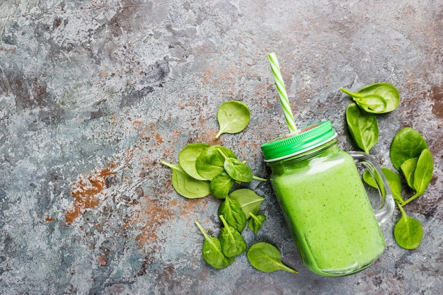 Smoothie vert sain aux épinards, avocat, banane et graines de chia dans des bocaux en verre sur fond de pierre grise, vue de dessus.