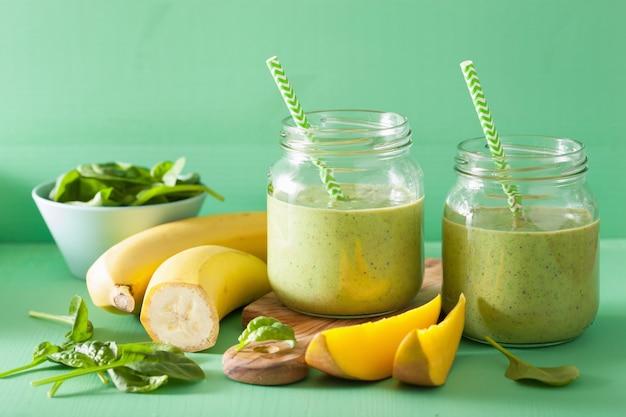 Smoothie vert sain avec banane mangue épinards dans des bocaux en verre
