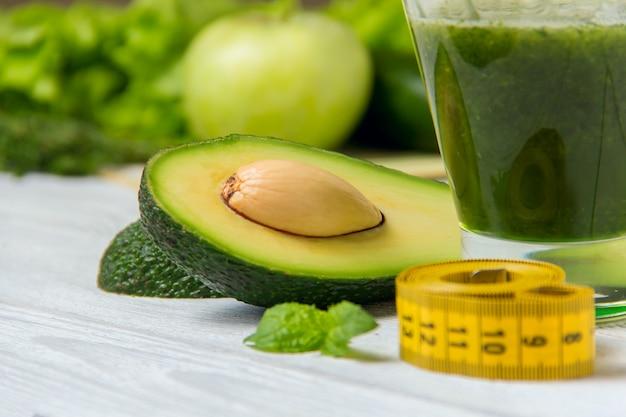 Smoothie vert sain avec des ingrédients sur bois blanc