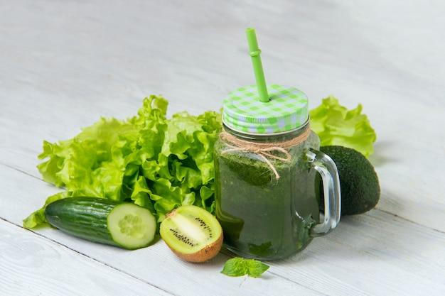Smoothie vert sain avec des ingrédients sur un fond en bois blanc