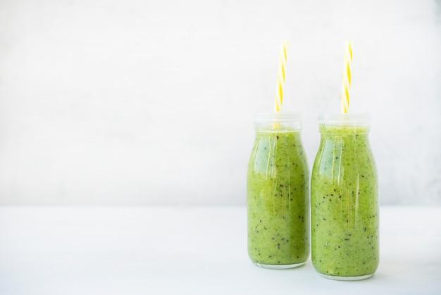 Smoothie vert végétarien avec des légumes et des fruits dans des bouteilles en verre sur fond blanc