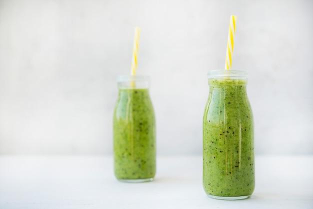 Smoothie vert végétarien avec des légumes et des fruits dans des bouteilles en verre, selective focus