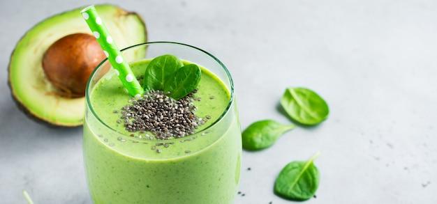 Smoothie vert végétarien sain à base d'avocat, de feuilles d'épinards, de pommes et de graines de chia en verre sur fond de béton gris. mise au point sélective. espace pour le texte. bannière.
