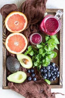Smoothie violet avec myrtilles, menthe, avocat et pamplemousse dans un plateau en bois. nourriture saine. petit déjeuner ou déjeuner d'été.