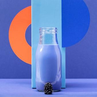 Smoothie vue de face dans une bouteille en verre avec des mûres