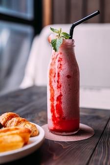 Smoothie de yogourt aux fraises dans une bouteille en verre avec des feuilles de menthe.
