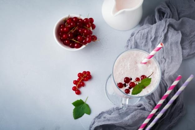 Smoothies au yaourt aux groseilles, milkshake dans une tasse en verre sur un fond de béton gris.