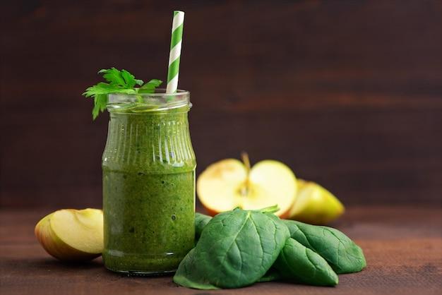 Smoothies aux épinards verts en verre avec des ingrédients sur une table en bois foncé.