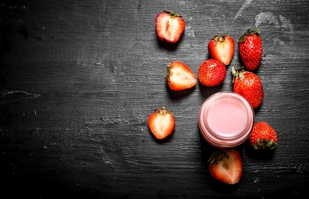 Smoothies aux fraises aux baies mûres. sur un fond en bois noir