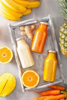 Smoothies aux fruits et légumes dans des bouteilles en verre