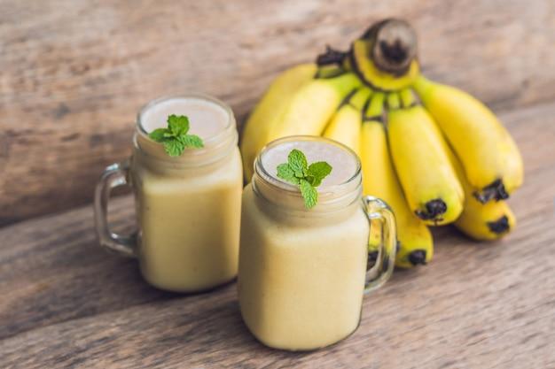Smoothies à la banane et bananes sur un vieux fond en bois.