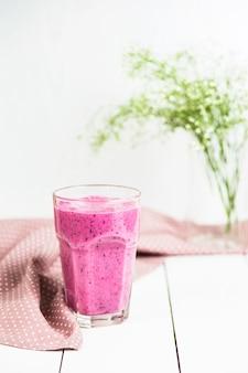 Smoothies banane et cassis dans un verre sur une table blanche à côté d'une serviette rose mouchetée