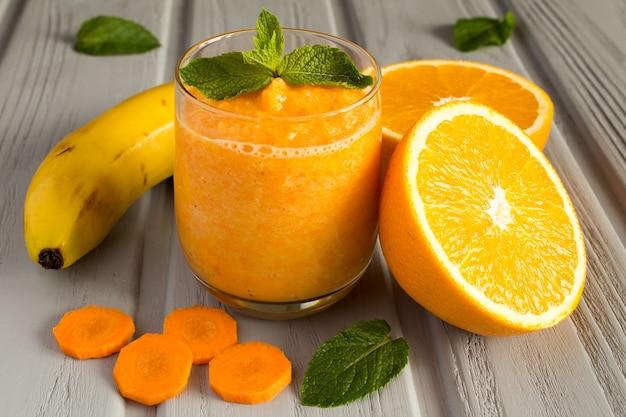Smoothies de banane, orange et carotte sur le fond en bois gris