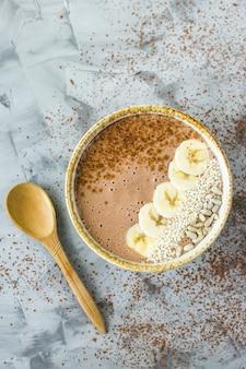 Smoothies chocolat-banane dans un bol sur un fond de béton gris