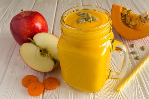 Smoothies à la citrouille, pomme et carotte sur le fond en bois blanc