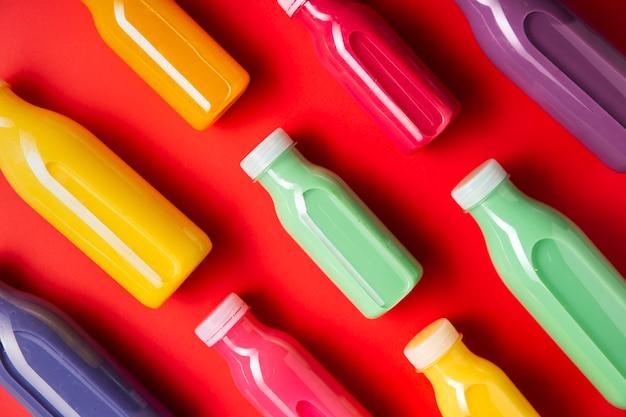 Smoothies colorés en diagonale sur fond rouge