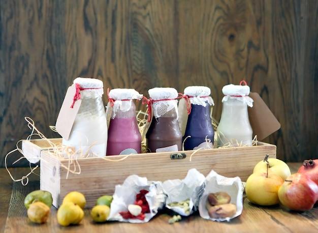 Smoothies colorés sains dans des bouteilles avec des fruits boivent du lait frappé dans une boîte en bois avec des ingrédients
