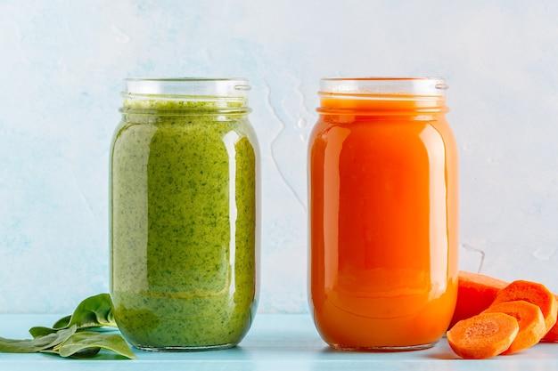 Smoothies de couleur orange et verte dans un pot isolé