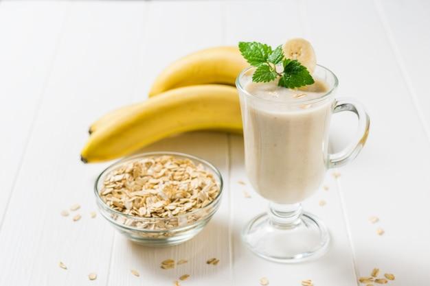 Smoothies dans un verre, flocons d'avoine et banane sur un tableau blanc