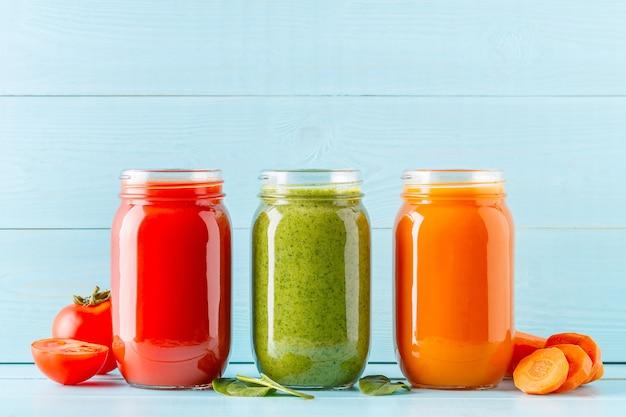 Smoothies / jus de couleur orange / vert / rouge dans un pot sur un bleu.