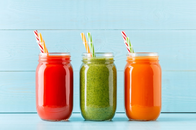 Smoothies / jus de couleur orange / vert / rouge dans un pot
