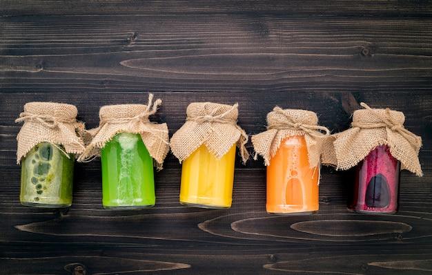 Smoothies et jus sains colorés en bouteilles avec des fruits tropicaux frais et des superaliments sur fond de bois.