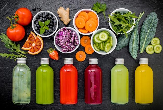 Smoothies et jus sains colorés dans des bouteilles avec des fruits tropicaux frais sur fond de pierre sombre.