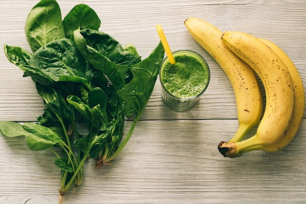 Smoothies avec une paille, une banane et des épinards feuilles sur un fond en bois blanc