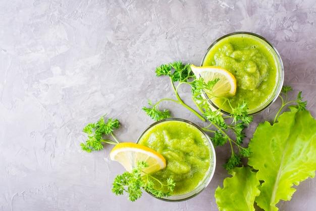 Smoothies rafraîchissants de concombre, pomme verte, herbes fraîches et jus de citron dans des verres transparents sur la table. le concept d'une alimentation saine. menu végétarien. vue de dessus