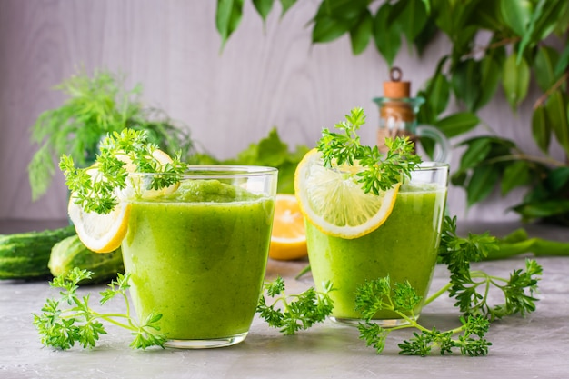 Smoothies rafraîchissants de concombre, pomme verte, herbes fraîches et jus de citron dans des verres transparents sur la table. le concept d'une alimentation saine. menu végétarien