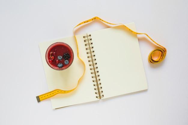 Smoothies rouges et ruban à mesurer sur le cahier à spirale sur fond blanc