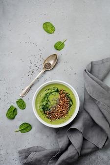 Smoothies utiles d'épinards avec des flocons de sarrasin dans des bols en céramique sur la surface de la table en béton gris