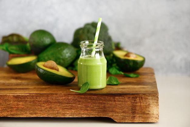 Smoothies verts à l'avocat et aux épinards dans une bouteille debout sur une table de cuisine, vue de face