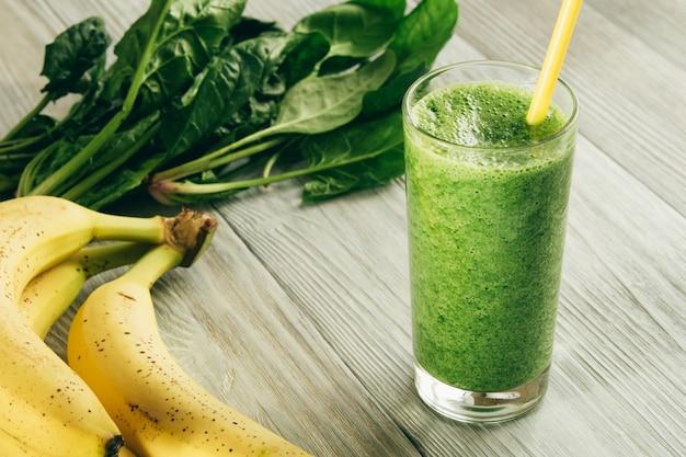 Smoothies verts d'épinards et de banane dans un verre avec de la paille jaune sur bois blanc