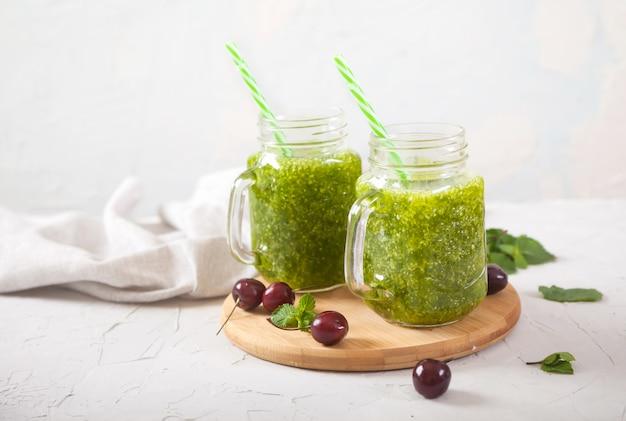 Smoothies verts frais dans des bocaux en verre et cerises douces sur un support en bois