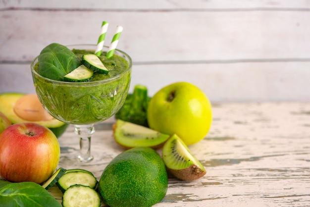 Smoothies verts avec des ingrédients sur une table en bois clair.