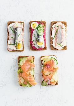 Smorrebrod de poisson savoureux, ensemble de cinq sandwichs danois traditionnels. pain de seigle noir