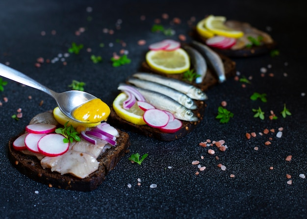 Smorrebrod, sandwichs traditionnels scandinaves avec pain de seigle noir, hareng, anchois, radis, oignons et sauce à la moutarde. gros plan, mise au point sélective.