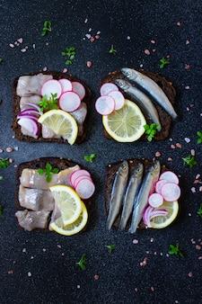 Smorrebrod, sandwichs traditionnels scandinaves avec pain de seigle noir, hareng, anchois, radis, oignons et sauce à la moutarde. vue de dessus