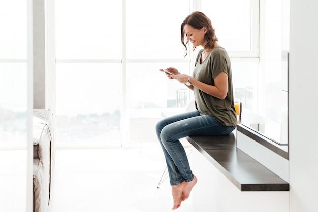 Sms de femme heureuse sur téléphone mobile