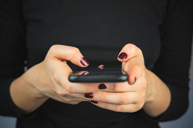 Sms sur le téléphone, à l'aide d'un smartphone. mains féminines avec un smartphone en tapant du texte et en faisant défiler