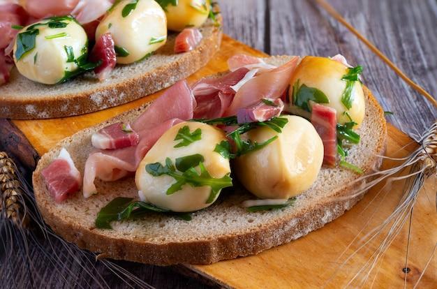 Snack apéritif avec pain complet, jambon cru et boules de provola fumées à l'huile