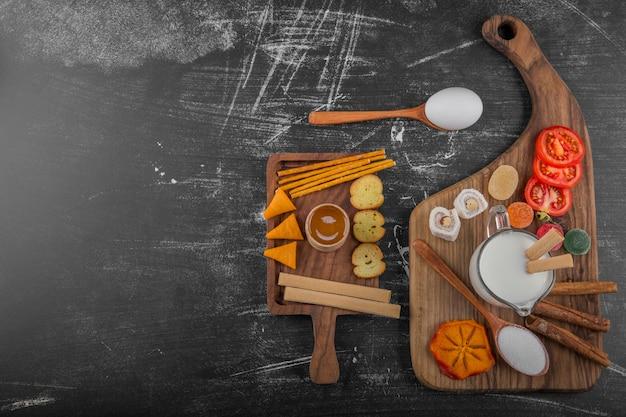 Snack board avec des craquelins et des légumes isolés sur fond noir