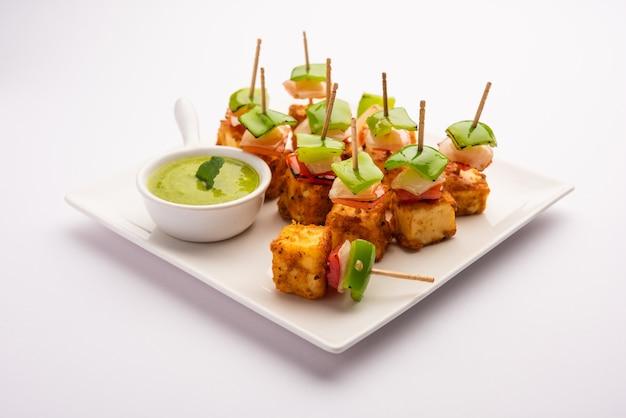 Snack de démarrage paneer tikka avec bâton dans la plaque avec chutney vert isolé sur blanc. plat de cuisine indienne avec du fromage cottage grillé avec des légumes et des épices
