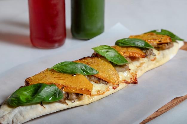Snack du moyen-orient aux saveurs de la méditerranée. citrouille au four, fromage scamorza affumicata, aubergine pochée et basilic frais sur planche de bois et jus naturels.