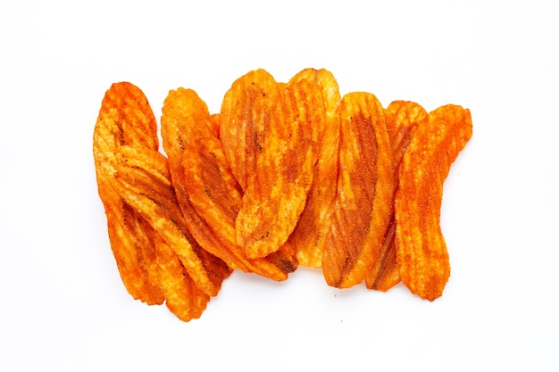 Snack épicé, banane tranche chips saveur paprika sur fond blanc.