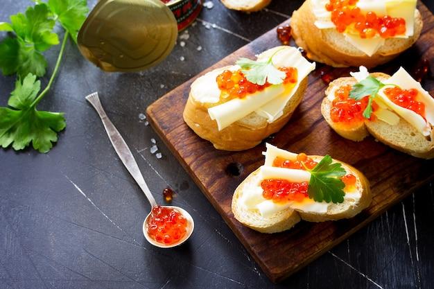 Snack festif sandwichs au caviar rouge isolé sur fond de béton foncé copy space