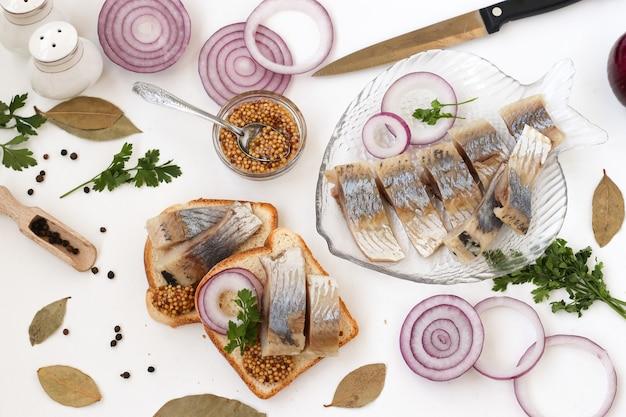 Snack de hareng salé sur du pain avec l'oignon rouge et la moutarde, vue du dessus.